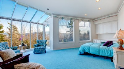 Great design for bedroom with glass wall. Blue carpet floor well matched with light blue bedding and white wood storage cabinets