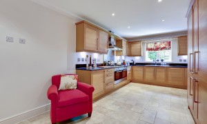 Modern fitted kitchen interior with built in appliances, granite worktops, tiled floor and red armchair